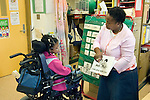 Oakland CA Aide helping developmentally disabled primary school student learn to read in special education classroom MR