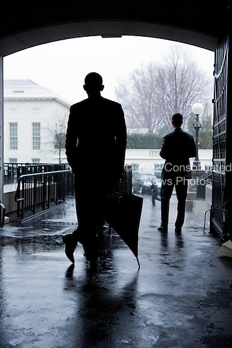 United States President Barack Obama waits for a heavy rain to pass before crossing West Executive Avenue from the Eisenhower Executive Office Building to the West Wing of the White House, March 12, 2013. .Mandatory Credit: Pete Souza - White House via CNP