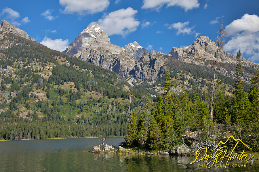 A boy jumps from rock to rock at Taggart Lake in Grand Teton National Park. Taggart Lake is a beautiful gem at the foot of the Grand Tetons of Jackson Hole Wyoming.