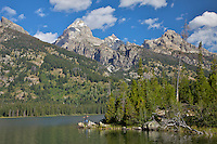 """A boy jumps from rock to rock at Taggart Lake in Grand Teton National Park. Taggart Lake is a beautiful gem at the foot of the Grand Tetons of Jackson Hole Wyoming.<br /> <br /> For production prints or stock photos click the Purchase Print/License Photo Button in upper Right; for Fine Art """"Custom Prints"""" contact Daryl - 208-709-3250 or dh@greater-yellowstone.com"""