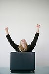 Businesswoman sitting in front of a laptop with her arms raised