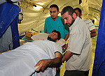A wounded rebel soldier is loaded aboard a ship in Misrata, the besieged Libyan city where civilians and rebel forces are surrounded on three sides by forces loyal to Libyan leader Moammar Gadhafi. The ship will carry him and other wounded, along with hundreds of fleeing African migrants, to the eastern Libyan city of Banghazi.