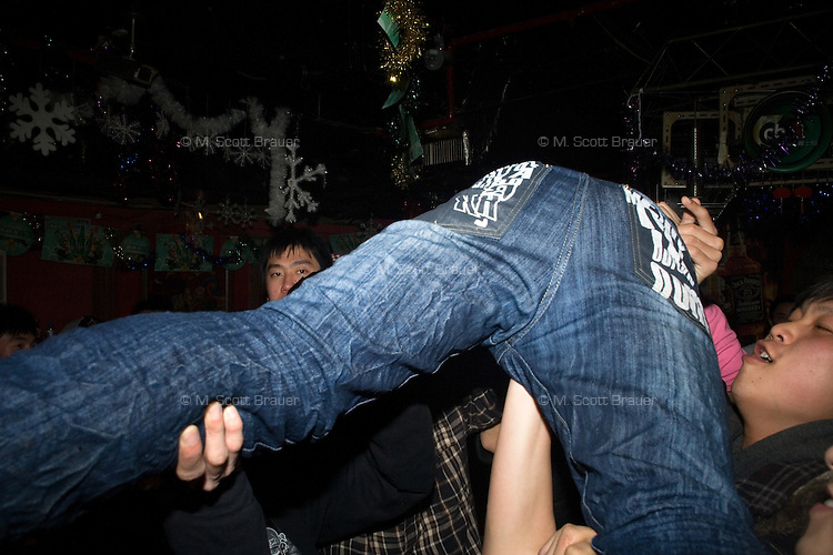 A punk rock fan crowd surfs during a concert at Castle Bar in Nanjing, China.