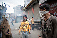 Srinagar, India-August 8, 2010: Kashmiri youths shield their faces from teargas during a stand-off with Indian police and military in downtown Srinagar