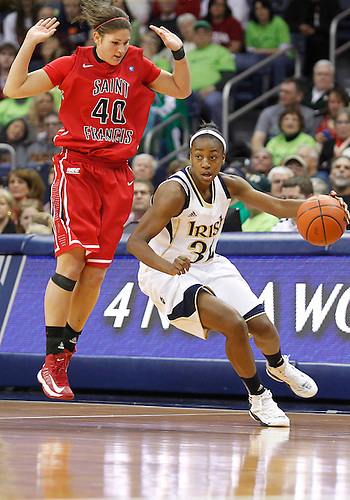 December 31, 2012:  Notre Dame guard Jewell Loyd (32) dribbles the ball as St. Francis center Alli Williams (40) defends during NCAA Women's Basketball game action between the Notre Dame Fighting Irish and the St. Francis (PA) Red Flash at Purcell Pavilion at the Joyce Center in South Bend, Indiana.  Notre Dame defeated St. Francis 128-55.