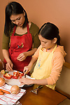 9 year old girl at home with mother in kitchen food preparation, cutting sweet red pepper