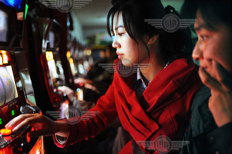 Young people gamble on a fruit machine in a bowling alley...