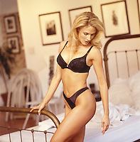 Photo of a beautiful Blond Woman standing next to a bed. She's wearing Black Lingerie.