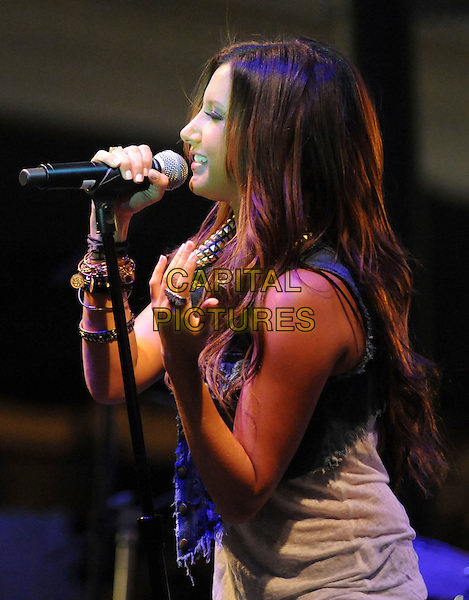 ASHLEY TISDALE .Performs Live at the Donate Life Concert Series at The Americana at Brand in Glendale, California, USA, .August 12th 2009..music gig concert live on stage performing half length microphone singing denim waistcoat jeans vest bracelets profile name ring knuckle duster .CAP/DVS.©DVS/RockinExposures/Capital Pictures