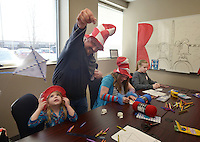 NWA Democrat-Gazette/BEN GOFF @NWABENGOFF<br /> Shannon Borkowski of Rogers flies around a kite made by his son Braxton Borkowski (from left), 3, as daughter Julia Borkowski, 12, and her 7th grade classmate Trinity Bania, 13, work on their kites Thursday, March 3, 2017, during the Read Across America Day event at Arkansas Connections Academy in Bentonville. Local students and their families made crafts before gathering to listen to recording artist Kris Allen read 'Go, Dog. Go!' by P.D. Eastman over the school's LiveLesson remote learning technology. The tuition-free virtual public charter school serving kindergarten through 9th grade students statewide is currently in it's first school year.
