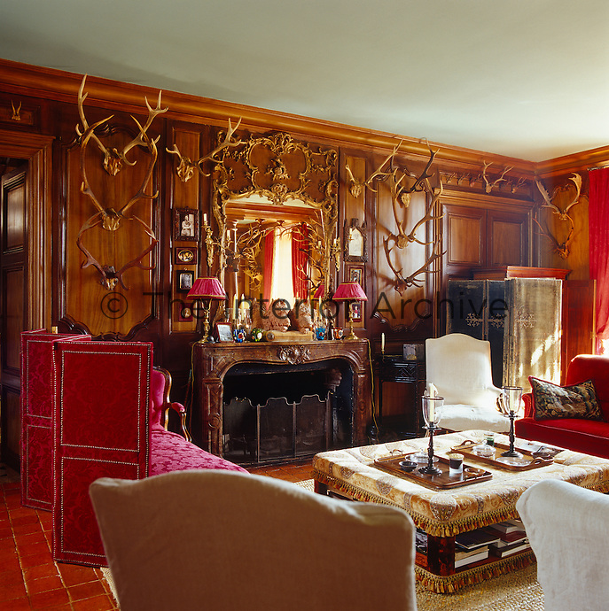An impressive collection of hunting trophies is displayed on the warm wooden panelling in the small private sitting room