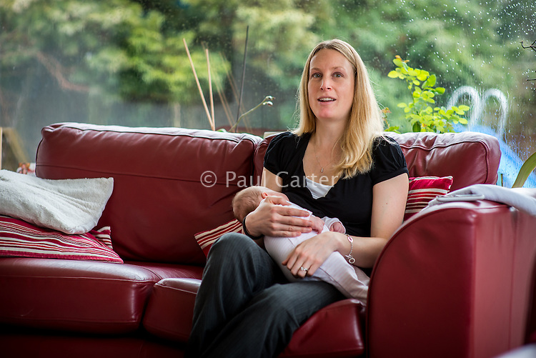 A woman sitting on her living room sofa and breastfeeding her 2 month old baby.<br /> <br /> Hampshire, England, UK<br /> 10/02/2013