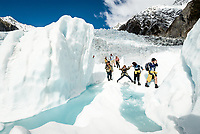 Group of guided tourists walking along beautiful turquoise melt water pools among ice blocks on Franz Josef Glacier. The Main Icefall in background, Westland Tai Poutini National Park, UNESCO World Heritage Area, West Coast, New Zealand, NZ