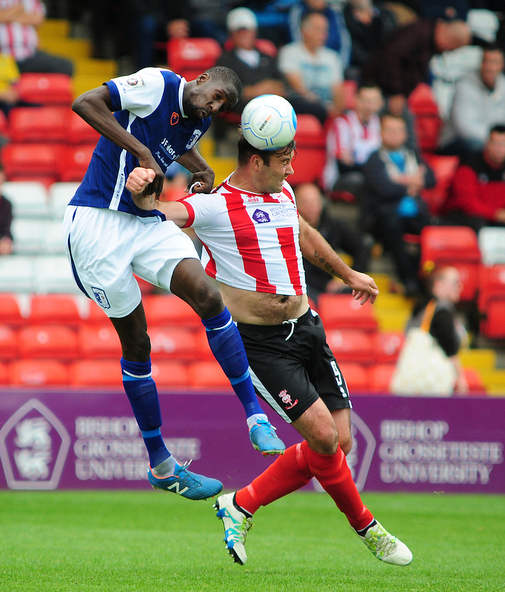 Barrow's Moussa Diarra vies for possession with Lincoln City's Matt Rhead<br /> <br /> Photographer Andrew Vaughan/CameraSport<br /> <br /> Vanarama National League - Lincoln City v Barrow - Saturday 17 September 2016 - Sincil Bank - Lincoln<br /> <br /> World Copyright &copy; 2016 CameraSport. All rights reserved. 43 Linden Ave. Countesthorpe. Leicester. England. LE8 5PG - Tel: +44 (0) 116 277 4147 - admin@camerasport.com - www.camerasport.com