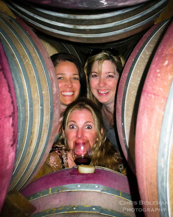 Three women looking through stacked wine barrels at a winery with a glass of wine smiling big and having fun