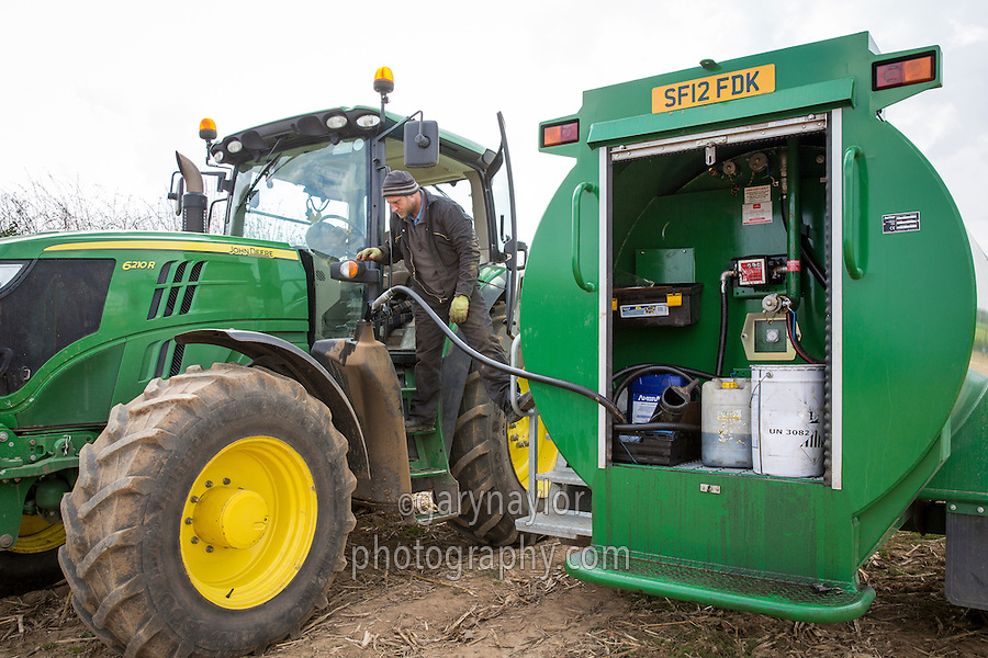 Filling a tractor in the field with diesel from a mobile bowser