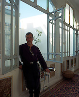 Jacques Montlucon standing at an open window of the traditional glassed-in gallery of his house in Damascus