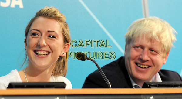 Boris Johnson and Laura Trott.Mayor Of London's Cycling Press Conference, London Media Centre, London, England..August 10th 2012.headshot portrait black white microphone table sitting smiling .CAP/BK.PP.©Bob Kent/PP/Capital Pictures.