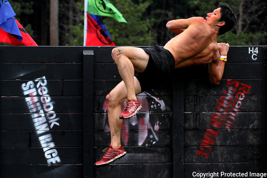 Junyoung Pak jumps over a wooden wall as he finishes the obstacle course at the Reebok Spartan race Invitational at Reebok Headquarters in Canton on Sunday April 27, 2014.(Photo by Gary Wilcox)