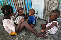 A girl feeds his younger brother by rice in the slum of Cité Soleil, Port-au-Prince, Haiti, 22 July 2008. Rice is a basic source of nutrition for all Haitians. Cité Soleil is considered one of the worst slums in the Americas, most of its 300.000 residents live in extreme poverty. Children and single mothers predominate in the population. Social and living conditions in the slum are a human tragedy. There is no running water, no sewers and no electricity. Public services virtually do not exist – there are no stores, no hospitals or schools, no urban infrastructure. In spite of this fact, a rent must be payed even in all shacks made from rusty metal sheets. Infectious diseases are widely spread as garbage disposal does not exist in Cité Soleil. Violence is common, armed gangs operate throughout the slum.