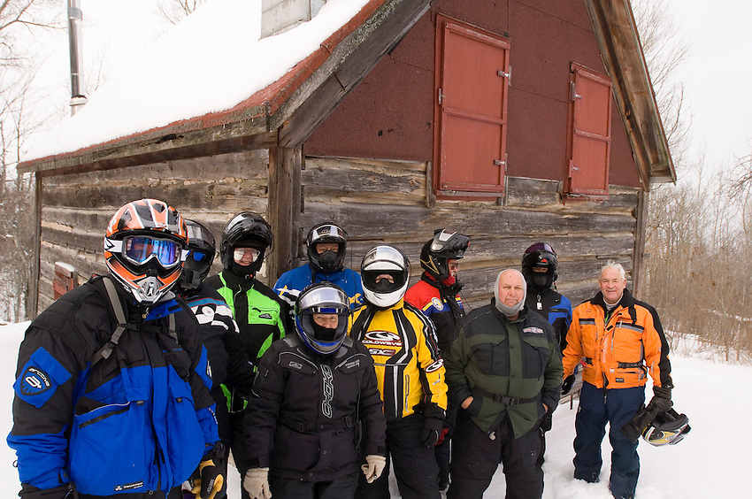 A group of snowmobilers from Decker Sno-Venture Tours pose for a photo in front of an old log cabin along the trail during a tour of the Keweenaw Peninsula on Michigan's Upper Peninsula.