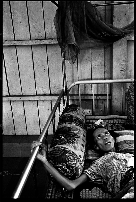 Siem Reap, Cambodia, December 2006..Sre Mok is in great pain, she doesn't have enough money even to buy cheap Chinese 'Tiger Balm' that can relieve her slightly from very severe chest and abdominal pains. She lives in very precarious conditions among dozens of TB patients in insalubrious barracks at the back of the Provincial Hospital compound. TB is endemic in the region, fueled by poverty, malnutrition, inadequate hygiene and the spreading of HIV/AIDS. The percentage of drug-resistant TB strains is on a sharp rise due to inadequate treatments.
