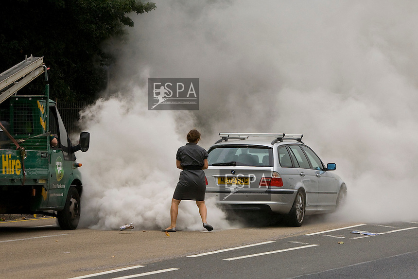 Aug 20 2009; Battersea London; A woman flees her car after it catches fire on Chelsea Bridge Road London