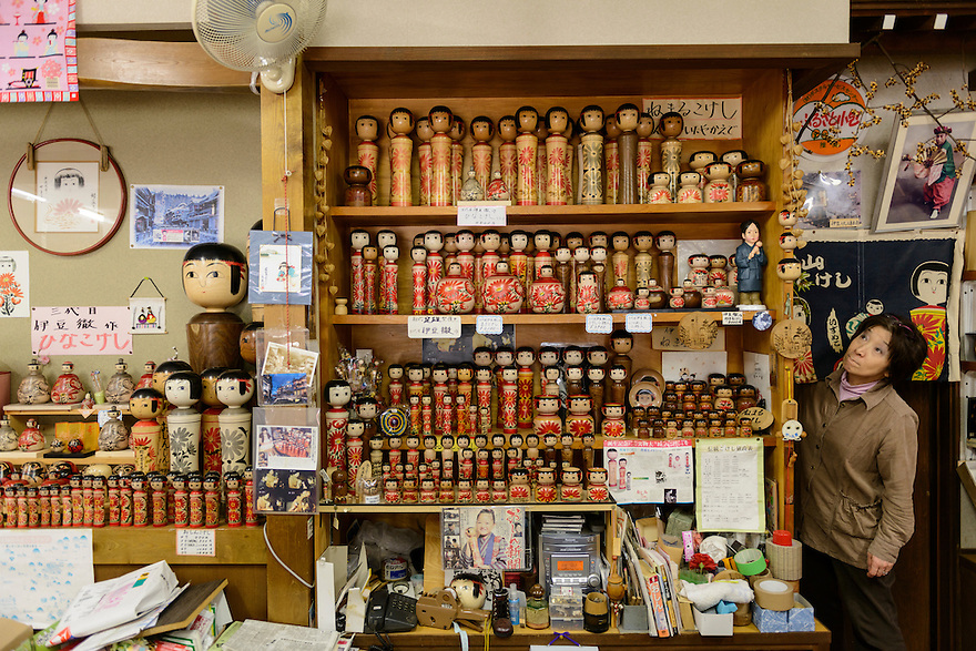 """A shop selling """"Kokeshi"""" wooden dolls and owner Shun Izu. Ginzan Onsen, Yamagata Prefecture, Japan, April 12, 2016. Once a sliver-mining town, Ginzan Onsen in Yamagata Prefecture is now one of Japan's best-known and most picturesque hot spring resorts. Its Taisho-period architecture and retro atmosphere is said to have been an inspiration for Hayao Miyazaki's Oscar-winning animated film, Spirited Away."""