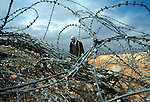 A woman crosses a barb wire fence in Kalandia, in the outskirts of Ramalah as she tries to avoid the Israeli army checkpoint March 11,2003.