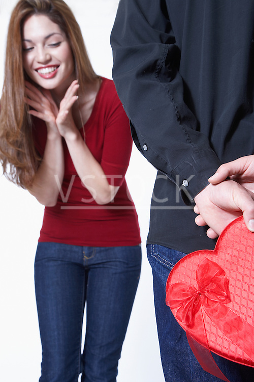Man hiding Valentine's gift in front of woman