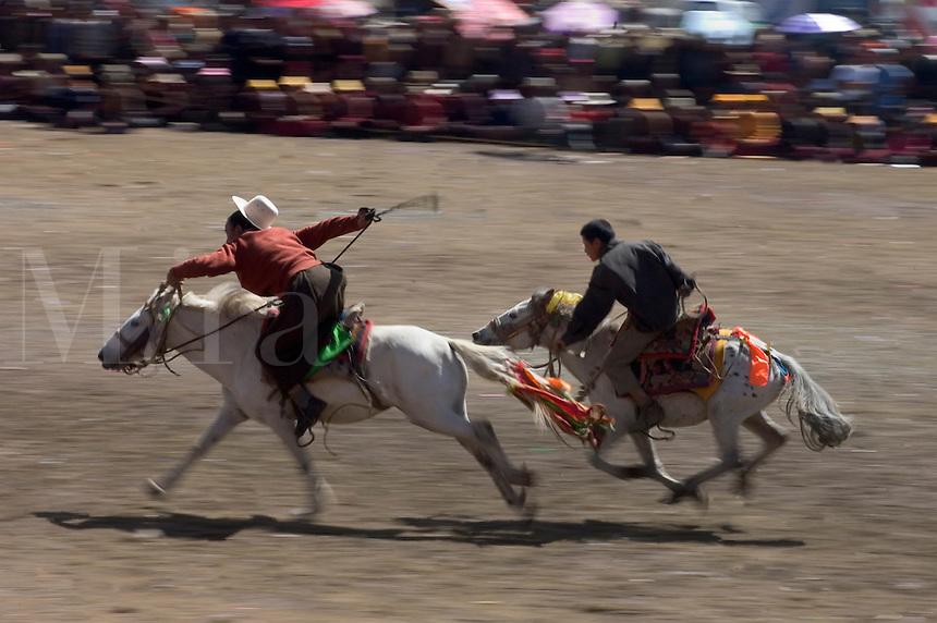 Khampa entertain the crowd in a rowdy horse race at the Litang Horse Festival - Kham, Sichuan Province, China, (Tibet)