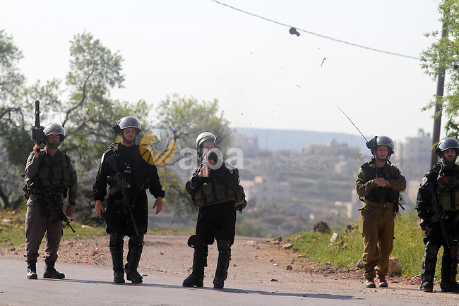 An Israeli security officer fires tear gas towards Palestinian protesters during clashes in the West Bank village of Silwad, north of Ramallah, on March 21, 2014 following a protest of Palestinians against the expansion of the nearby Israeli settlement of Ofra. Photo by Issam Rimawi