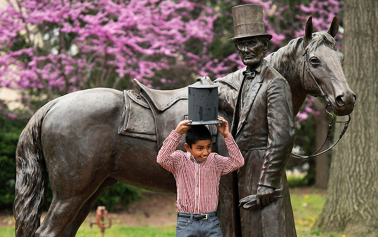 UNITED STATES - APRIL 22: Pratyush Jaishanker, 10, originally from India, poses for a picture with a statue of Abraham Lincoln, before a citizenship ceremony at President Lincoln's Cottage in Northwest. Twenty children from fifteen countries, who recently became citizens, participated in a swear-in ceremony. (Photo By Tom Williams/CQ Roll Call)