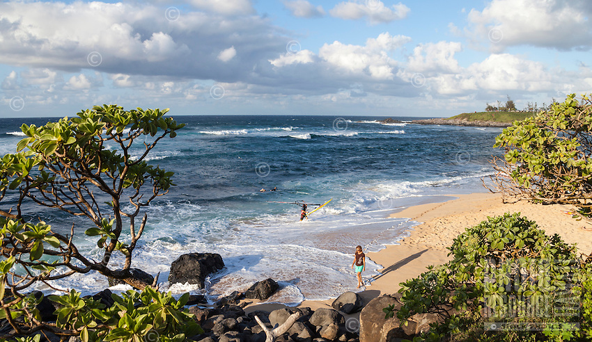 A woman strolls past foamy waves at Ho'okipa Beach, Maui; in the distance, a windsurfer brings his board to shore and a surfer waits for a wave.