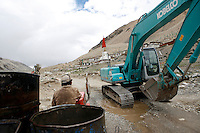 China started building a controversial 67-mile &quot;paved highway fenced with undulating guardrails&quot; to Mount Qomolangma, known in the west as Mount Everest, to help facilitate next year's Olympic Games torch relay./// Two workers gather water and bring it to the construction site on the road to EBC. <br /> Tibet, China<br /> July, 2007