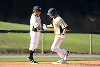Central Florida Knights infielder Tommy Williams (14) congratulated by coach Kevin Schnall (9) after hitting a home run during a game against the Siena Saints at Jay Bergman Field on February 16, 2014 in Orlando, Florida.  UCF defeated Siena 9-6.  (Mike Janes/Four Seam Images)