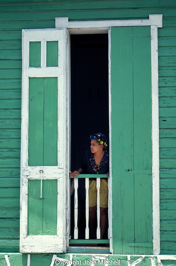 Woman standing in the window of a typical Caribbean-style wooden house in the town of Barahona, Dominican Republic