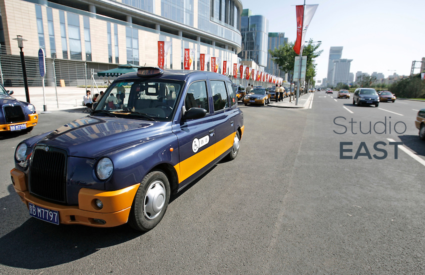 A TX4 London Taxi cab with wheelchair access waits for customers in Beijing, China during the 2008 Paralympics Games, on September 11, 2008. About 30 new wheelchair accessible TX4 London taxis, painted with the traditional colors of Beijing taxis, have been placed into service during the  Paralympic Games and will remain in the city afterwards. London Taxi International, the producer of London Taxi's famed black cabs, turned to China to drive overseas expansion. More than 8,000 London Taxis will be produced from the Chinese factory, more than double the annual output of the firm's historical factory plant in Conventry, England. Most of these cars will go to places like Singapore, Dubai, Moscow, that covet the image associated with the London Taxis' tradition of good service and durability. London Taxi International will continue to build 90 percent of the Taxi cabs used in Britain at Coventry. Photo by Lucas Schifres/Pictobank