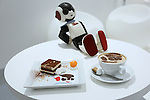 """A communication robot called """"Robi"""" is seated behind a """"Robi latte"""" and """"Robi's tiramisu plate"""", inspired by the robot, during a press preview for """"Robi cafe"""" where visitors can interact with the robots while enjoying meals and drinks in Tokyo, Thursday, January 15, 2015. The robot can be built by assembling parts sent along with a weekly magazine by Deagostini. The cafe will open from January 16 until February 8. (Photo by Yuriko Nakao/AFLO)"""