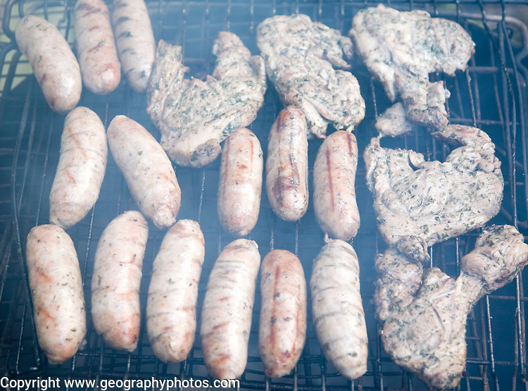 Sausages and beef burgers cooking on barbecue grill