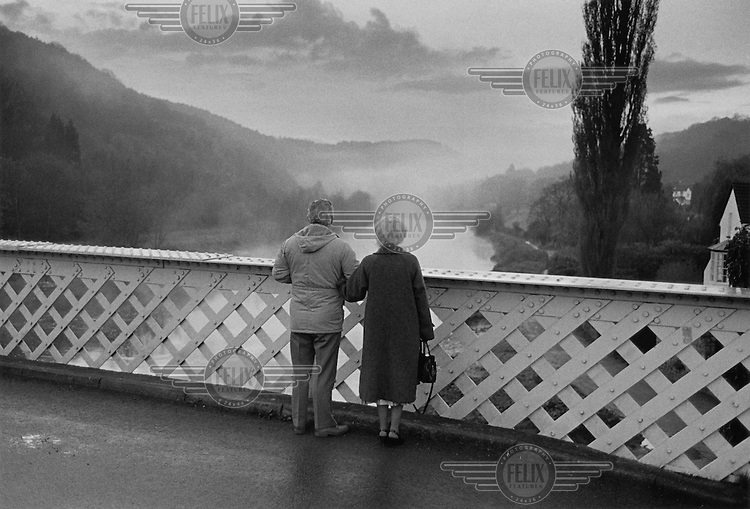 A couple on the bridge over the river Wye in Brockweir, Gloucestershire.