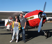 A family poses in front of Marlon Young's Cessna 195 during the  Experimental Aircraft Association Young Eagles rally at Lampson Field (102), Lakeport, Lake County, California