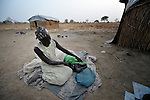 A woman covers her child as they awake in the morning after sleeping outside on the ground in front of their rustic shelter in Agok, a town in the contested Abyei region where tens of thousands of people fled in 2011 after an attack by soldiers and militias from the northern Republic of Sudan on most parts of Abyei. Although the 2005 Comprehensive Peace Agreement called for residents of Abyei--which sits on the border between Sudan and South Sudan--to hold a referendum on whether they wanted to align with the north or the newly independent South Sudan, the government in Khartoum and northern-backed Misseriya nomads, excluded from voting as they only live part of the year in Abyei, blocked the vote and attacked the majority Dinka Ngok population. The African Union has proposed a new peace plan, including a referendum to be held in October 2013, but it has been rejected by the Misseriya and Khartoum. The Catholic parish of Abyei, with support from Caritas South Sudan and other international church partners, has maintained its pastoral presence among the displaced and assisted them with food, shelter, and other relief supplies.