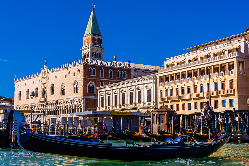 Gondolier rowing his gondola with Doge's Palace behind, Venice, Italy.