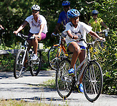 Sasha Obama, 10, (R) daughter of United States President Barack Obama and Frst Lady Michelle Obama (L) bike together on a bike path through Manuel F. Correllus State Forest in West Tisbury, Massachusetts while vacationing on Martha's Vineyard on August 23, 2011.    .Credit: Matthew Healey / Pool via CNP