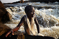 A young girl, catching fish among the low season rapids, rests on a rock at Boyoma Falls (known locally as Wagenia Falls). In order to keep her hands free she keeps the fish in her mouth. This is the last of seven cataracts below which the Lualaba River becomes the Congo. For generations members of the Wagenia tribe have fished here using great wooden scaffolds and traps in the same manner described by Henry Morton Stanley, after whom the falls were also once named, during his navigation of the Congo in 1874-77.