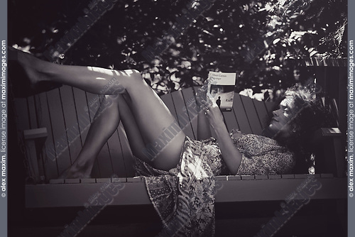 Sensual black and white artistic portrait of a beautiful young woman reading a book lying on a garden bench in a shade