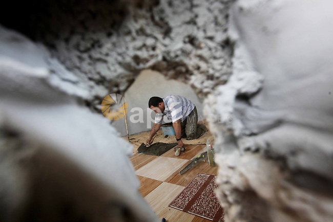 A Palestinian laborer works in flooring during the holy month of Ramadan, in Deir al-Balah in central Gaza Strip on 02 August  2012. During Ramadan, eating, drinking, sex and smoking is banned and restaurants are forbidden to serve food during the fasting hours. Photo by Ashraf Amra