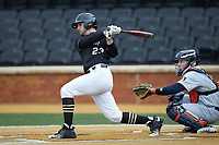 Jake Mueller (23) of the Wake Forest Demon Deacons follows through on his swing against the Illinois Fighting Illini at David F. Couch Ballpark on February 16, 2019 in  Winston-Salem, North Carolina.  The Fighting Illini defeated the Demon Deacons 5-2.  (Brian Westerholt/Four Seam Images)