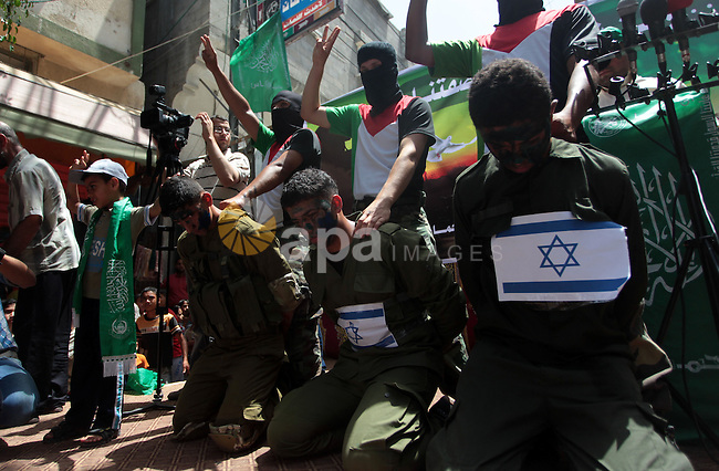 Palestinian Hamas supporters dressed as Israeli soldiers in a scene that alludes to the kidnapping of three Israeli teenagers during a demonstration in solidarity with prisoners held in Israeli jails, and in support of the people in the West Bank, in Nuseirat refugee camp in the center of the Gaza Strip, June 20, 2014. Israel has launched a wide-ranging military operation aimed at finding the Israeli teenagers that believed kidnapped by Hamas and crushing the movement's infrastructure in the West Bank. Photo by Ashraf Amra